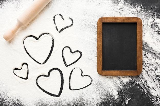 Vista superior de formas de coração em farinha com quadro-negro