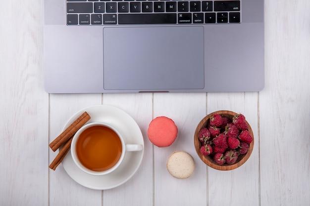 Vista superior de framboesas com uma xícara de biscoitos de chá e um laptop em uma superfície branca