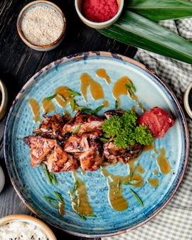 Vista superior de frango assado com ervas frescas de tomate grelhado e molho num prato de madeira