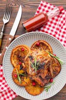 Vista superior de frango assado e fatias de laranja no prato com talheres e molho
