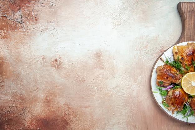 Vista superior de frango, cebola, ervas, limão e pedaços de frango no tabuleiro