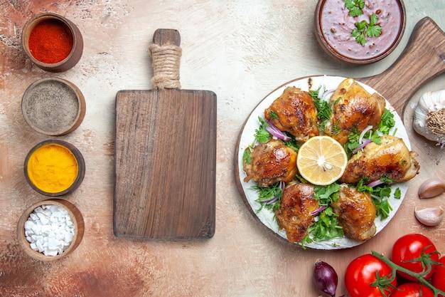 Vista superior de frango com molho de especiarias de frango com ervas, cebola, tomate, tábua