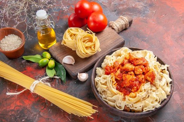 Vista superior de frango com prato de massa com tomates em uma refeição de massa escura de mesa