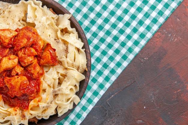 Vista superior de frango com prato de massa de massa no prato de massa de refeição de cor escura