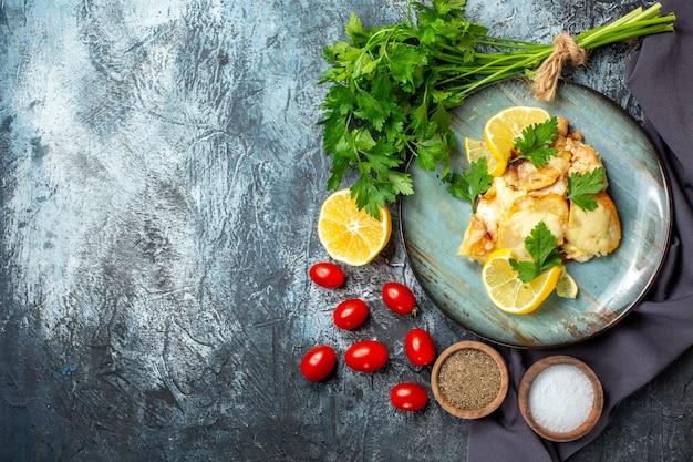 Vista superior de frango com queijo no prato molho de salsa, limão, tomate cereja, especiarias em tigelas na mesa cinza com local de cópia