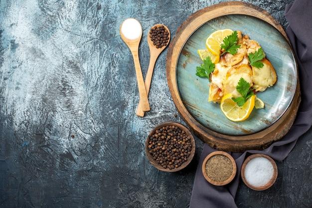 Vista superior de frango com queijo no prato na placa de madeira temperos em colheres de madeira no espaço livre da mesa cinza