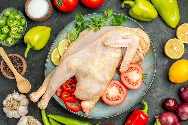 Vista superior de frango cru fresco com diferentes vegetais na mesa escura refeição salada madura alimentação saúde dieta