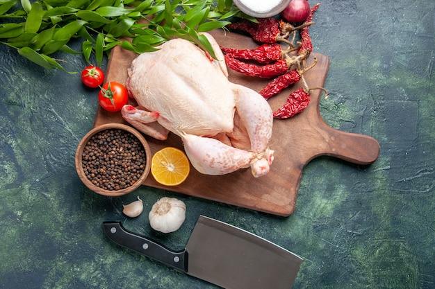 Vista superior de frango cru fresco com tomates vermelhos em fundo azul escuro refeição de cozinha foto animal comida frango cor de carne