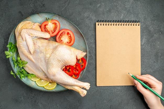 Vista superior de frango fresco cru dentro do prato com verduras e legumes em fundo escuro