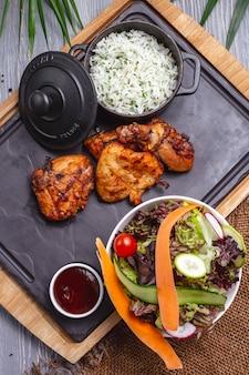 Vista superior de frango frito com arroz em uma panela com molho e salada de legumes