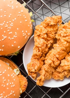 Vista superior de frango frito e hambúrgueres na bandeja