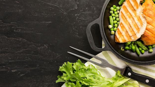 Vista superior de frango grelhado com ervilhas na panela com cópia-espaço