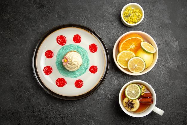 Vista superior de frutas ao longe e placa de chocolate com bolinho com creme branco e molhos ao lado das tigelas de ervas e limões fatiados e xícara de chá