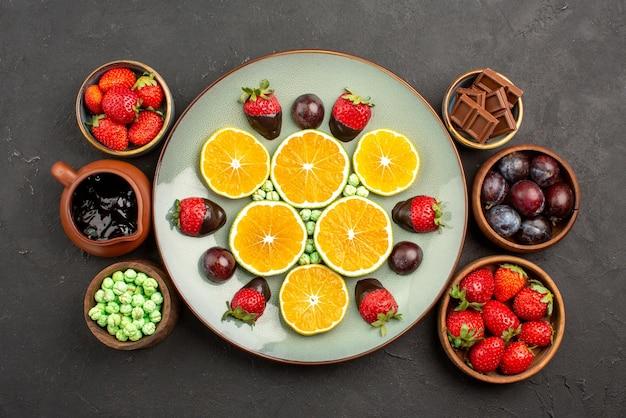 Vista superior de frutas ao longe e placa de chocolate com morangos cobertos de chocolate e laranja picada ao lado das tigelas de doces com calda de chocolate e frutas vermelhas na mesa