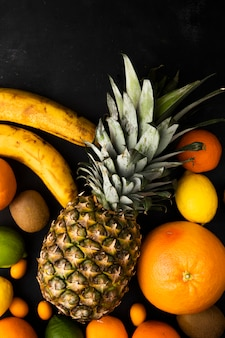 Vista superior de frutas cítricas como banana abacaxi laranja e outros na superfície preta
