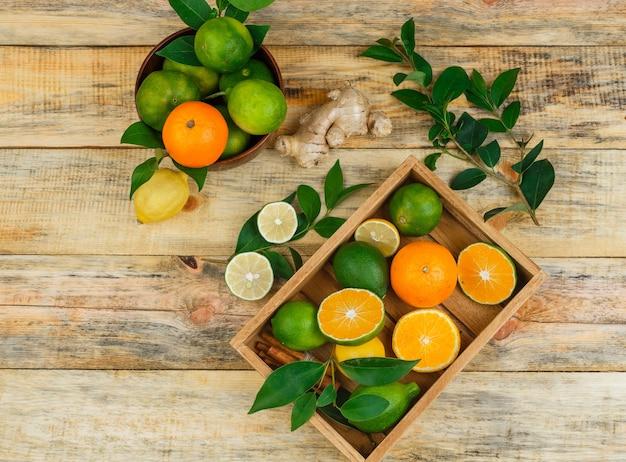 Vista superior de frutas cítricas em uma tigela de madeira e uma caixa com folhas e gengibre