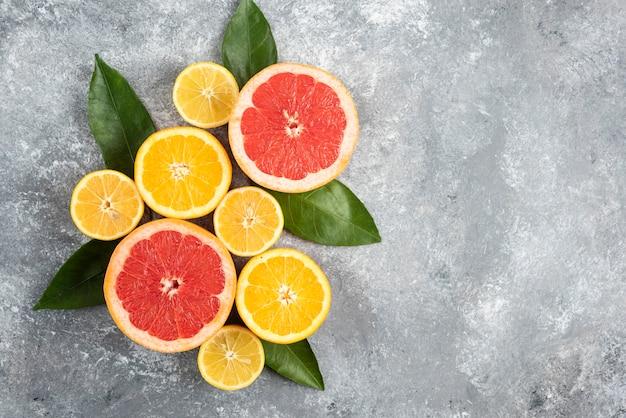 Vista superior de frutas cítricas frescas, frutas cortadas pela metade na mesa cinza.