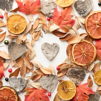 Vista superior de frutas cítricas secas com folhas de outono e formato de coração