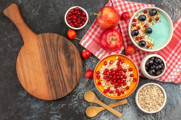 Vista superior de frutas, colheres, maçãs, bagas coloridas, aveia, romã, tábua de cortar