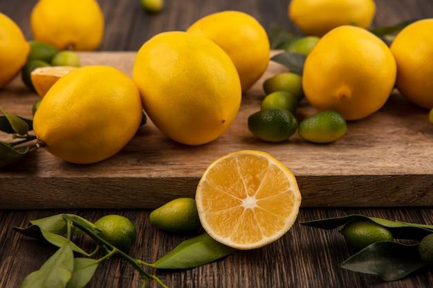 Vista superior de frutas coloridas, como kinkans e limões em uma placa de cozinha de madeira em uma parede de madeira