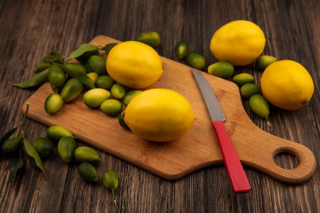 Vista superior de frutas coloridas, como limões e kinkans em uma placa de cozinha de madeira com uma faca na parede de madeira
