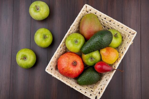 Vista superior de frutas coloridas, como maçã, pêra, manga no balde, com maçãs verdes na madeira