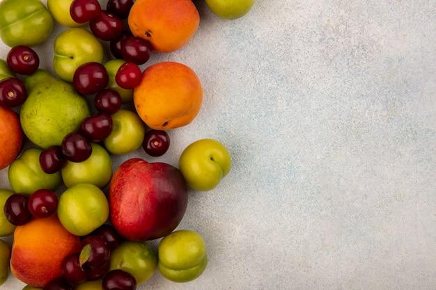 Vista superior de frutas como ameixa, pêssego, cereja e pêra, no fundo branco com espaço de cópia