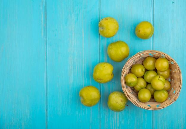 Vista superior de frutas como ameixas na cesta e padrão de pluots verdes sobre fundo azul com espaço de cópia