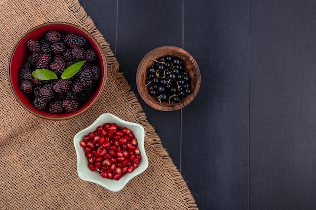 Vista superior de frutas como bagas de amora e romã em taças de saco com tigela de bagas de abrunheiro na superfície preta