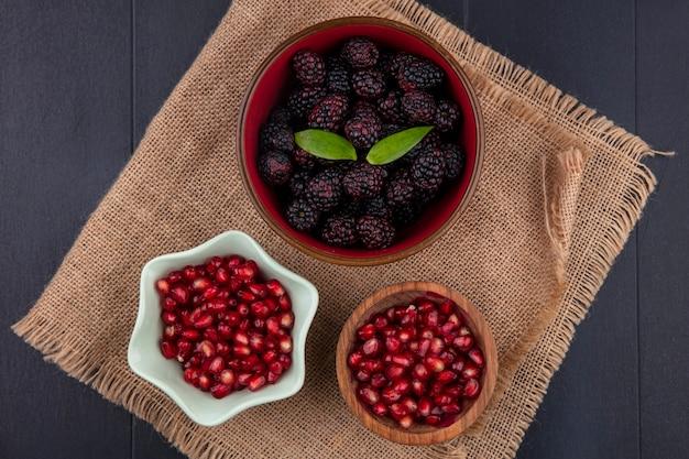 Vista superior de frutas como bagas de amora e romã em taças de saco e superfície preta