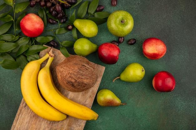 Vista superior de frutas como banana, coco na tábua e uva, pêssego, maçã, pêra, com folhas em fundo verde