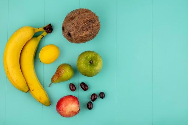 Vista superior de frutas como banana, maçã, limão, pêssego, uvas, pêra, coco, sobre fundo azul com espaço de cópia