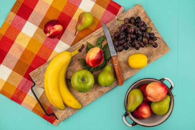 Vista superior de frutas como banana maçã pêssego pêra limão uva com faca e folhas em uma tábua de corte em tecido xadrez com pote de pêssego pera no fundo azul
