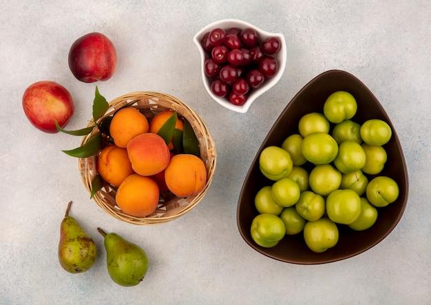 Vista superior de frutas como cereja e ameixa em uma cesta e tigelas com pêssegos e peras no fundo branco