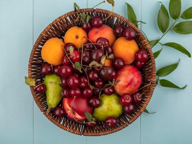 Vista superior de frutas como cereja, pêssego, pêra, damasco, em uma cesta com folhas em fundo azul