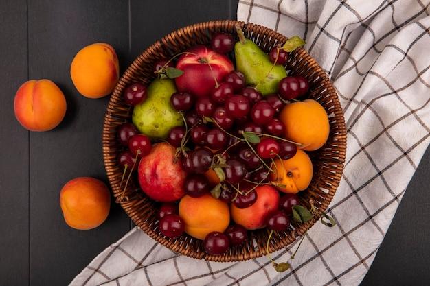 Vista superior de frutas como cereja, pêssego, pêra, damasco, em uma cesta em tecido xadrez e em fundo preto