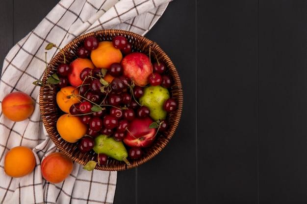 Vista superior de frutas, como cereja, pêssego, pêra, damasco, na cesta e em tecido xadrez em fundo preto com espaço de cópia