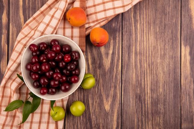 Vista superior de frutas como cerejas em uma tigela com damascos, ameixas e folhas em pano xadrez e fundo de madeira com espaço de cópia