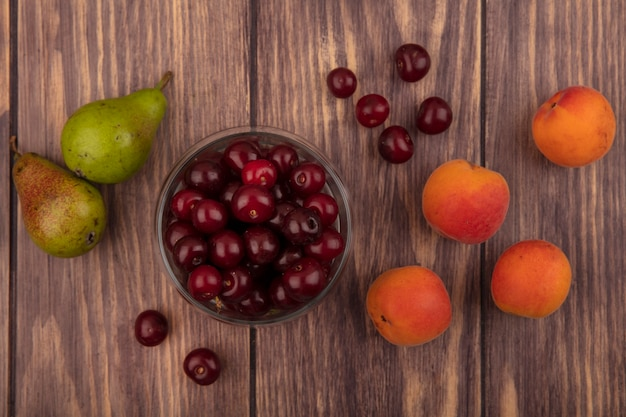 Vista superior de frutas como cerejas em uma tigela e padrão de peras, damascos, cerejas em fundo de madeira
