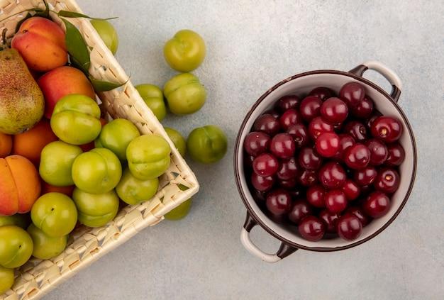 Vista superior de frutas como cerejas em uma tigela e uma cesta de ameixa de damasco de pêra no fundo branco