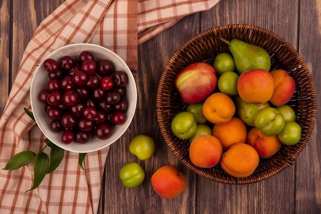 Vista superior de frutas como cerejas em uma tigela sobre um pano xadrez e uma cesta de ameixa de pera de damasco pêssego em fundo de madeira