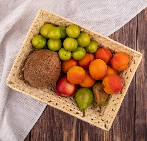 Vista superior de frutas como coco, ameixa, damasco, pêssego, pêra em uma cesta em um pano branco sobre fundo de madeira