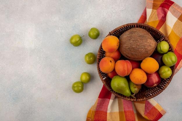 Vista superior de frutas como coco, damasco, pêssego, pêra, em uma cesta em pano xadrez com ameixas no fundo branco com espaço de cópia