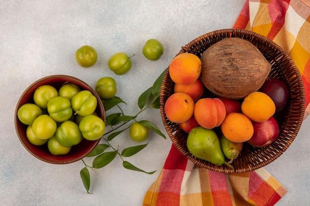 Vista superior de frutas como coco, damasco, pêssego, pêra, em uma cesta em pano xadrez com uma tigela de ameixas no fundo branco