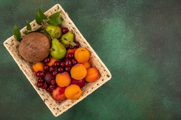 Vista superior de frutas como coco, pêssego, damasco, pera cereja, com folhas na cesta sobre fundo verde com espaço de cópia