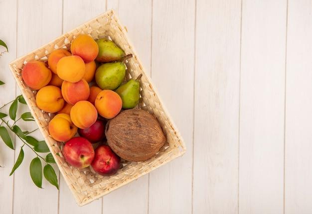 Vista superior de frutas como coco, pêssego, pêra, em uma cesta com folhas em fundo de madeira com espaço de cópia