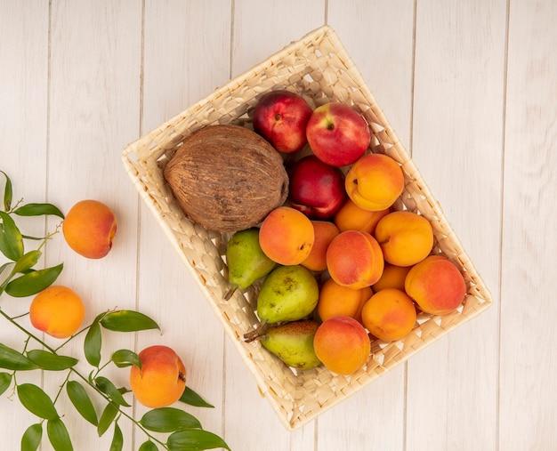 Vista superior de frutas como coco, pêssego, pêra em uma cesta com folhas no fundo de madeira