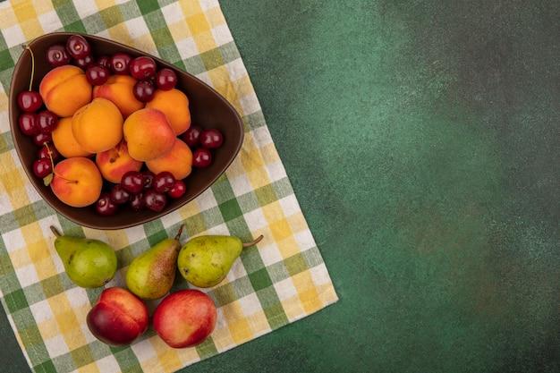 Vista superior de frutas como damasco e cereja em uma tigela e padrão de peras e pêssegos em tecido xadrez em fundo verde com espaço de cópia