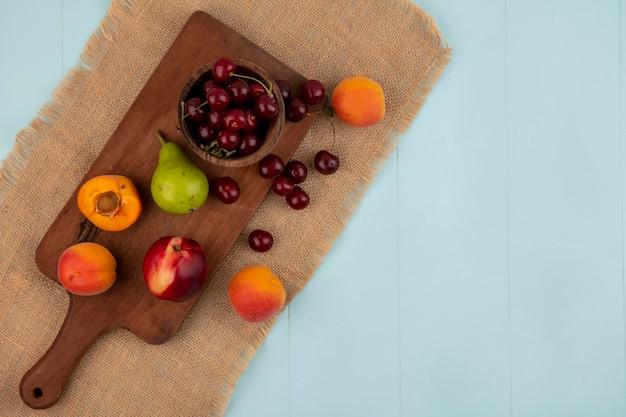 Vista superior de frutas como damascos, pêssego, pêra e tigela de cereja, na tábua e no saco no fundo azul com espaço de cópia