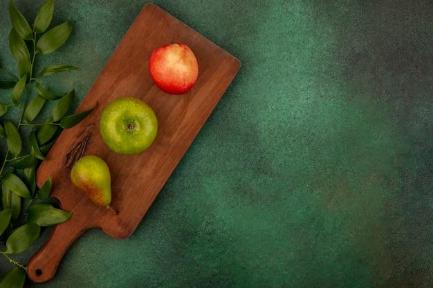 Vista superior de frutas como maçã, pêssego, pêra, numa tábua, com folhas em fundo verde com espaço de cópia